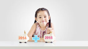 Kleines Mädchen, das Geld auf ein Sparschwein mit einem neuen Jahr 2015 steckt Lizenzfreie Stockbilder