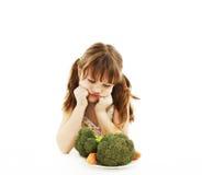 Kleines Mädchen, das Gemüse ablehnt lizenzfreies stockbild
