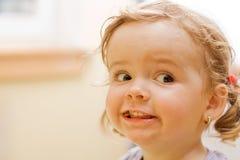 Kleines Mädchen, das Gesichter bildet lizenzfreies stockbild