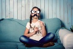 Kleines Mädchen, das Gesichter mit Schnurrbartstützen macht Stockfotografie