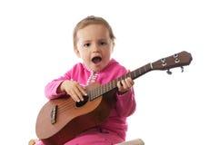 Kleines Mädchen, das Gitarre spielt. Lizenzfreies Stockfoto