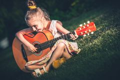 Kleines Mädchen, das Gitarre spielt Stockfotografie