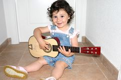 Kleines Mädchen, das Gitarre spielt Stockfoto