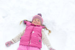 Kleines Mädchen, das glücklich im Schnee spielt Stockfotografie