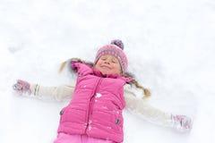 Kleines Mädchen, das glücklich im Schnee spielt Lizenzfreie Stockfotos
