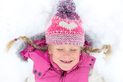 Kleines Mädchen, das glücklich im Schnee spielt Stockfoto