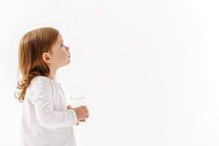 Kleines Mädchen, das Glas mit Flüssigkeit hält Stockfotos