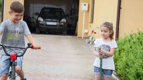 Kleines Mädchen, das grünes Gras im Garten wässert Nettes kleines Mädchen hält das Besprühung und sprüht den Rasen auf a stock video footage