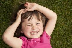 Kleines Mädchen, das in Gras legt stockfoto