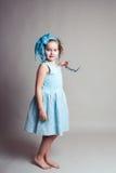 Kleines Mädchen, das in Gray Backdrop steht stockfoto
