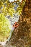 Kleines Mädchen, das großen Baum umarmt stockbild