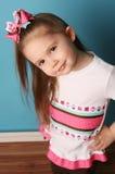 Kleines Mädchen, das Haarbogen formt und Hemd abgleicht Stockfoto