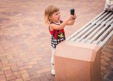 Kleines Mädchen, das Handy schaut Stockfoto