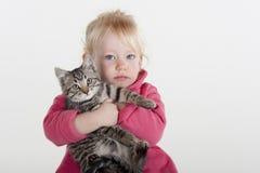 Kleines Mädchen, das Haustierkätzchen umarmt Lizenzfreie Stockbilder