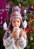 Kleines Mädchen, das heiße Schokolade trinkt Stockbild