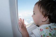 Kleines Mädchen, das heraus Fenster des Flugzeuges schaut Stockfotos