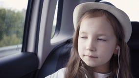 Kleines Mädchen, das heraus vom Autofenster sonnigem Tag betrachtet stock footage