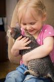 Kleines Mädchen, das het-Katze umarmt Lizenzfreies Stockfoto