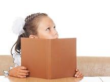 Kleines Mädchen, das hinter Buch sich versteckt Lizenzfreies Stockbild