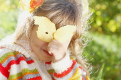 Kleines Mädchen, das hinter dem Blatt am sonnigen Tag sich versteckt Lizenzfreie Stockbilder