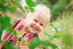 Kleines Mädchen, das hinter dem Laub sich versteckt Lizenzfreie Stockbilder