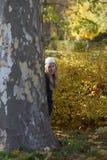 Kleines Mädchen, das hinter einem Baum sich versteckt lizenzfreies stockfoto