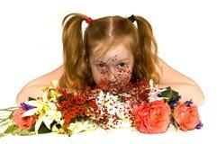 Kleines Mädchen, das hinter einige Blumen legt Stockbild