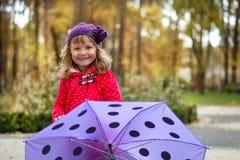 Kleines Mädchen, das hinter purpurrotem Regenschirm steht Lizenzfreies Stockfoto