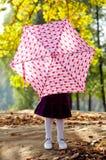 Kleines Mädchen, das hinter Regenschirm sich versteckt Lizenzfreies Stockbild