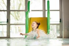 Kleines Mädchen, das hinunter die Wasserrutsche schiebt Lizenzfreie Stockfotos