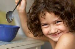 Kleines Mädchen, das ihr Frühstück einnimmt Lizenzfreie Stockfotos