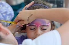 Kleines Mädchen, das ihr Gesicht gemalt vom Gesichtsmalereikünstler erhält Stockbilder