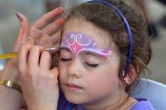 Kleines Mädchen, das ihr Gesicht gemalt vom Gesichtsmalereikünstler erhält Stockfoto