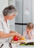 Kleines Mädchen, das ihr Großmutterkochen betrachtet stockfotos