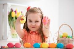 Kleines Mädchen, das ihr handgemalte bunte Eier zeigt stockfotos