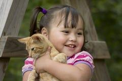 Kleines Mädchen, das ihr Kätzchen umarmt Stockbild