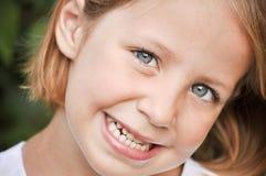 Kleines Mädchen, das ihr weiße Zähne zeigt Lizenzfreie Stockfotografie