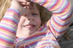 Kleines Mädchen, das ihre Augen von der Sonne abschirmt. Stockfoto