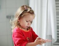 Kleines Mädchen, das ihre Hände wäscht Lizenzfreie Stockfotografie