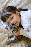 Kleines Mädchen, das ihre Katze umarmt Stockbilder