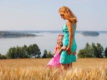 Kleines Mädchen, das ihre Mutter auf einem Weizengebiet nahe See umarmt Stockfotografie