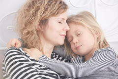 Kleines Mädchen, das ihre Mutter beim Schlafen umarmt Lizenzfreie Stockfotografie