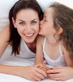 Kleines Mädchen, das ihre Mutter liegt auf Bett küßt lizenzfreie stockfotos