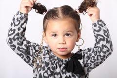 Kleines Mädchen, das ihre Pferdeschwänze hält. Stockbild