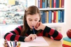 Kleines Mädchen, das ihre Schulhausarbeit tut lizenzfreie stockfotografie