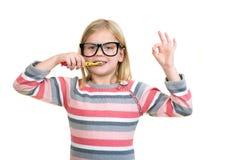 Kleines Mädchen, das ihre Zähne lokalisiert auf weißem Hintergrund putzt Stockbild
