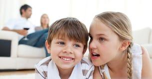 Kleines Mädchen, das ihrem Bruder ein Geheimnis erklärt Stockfoto