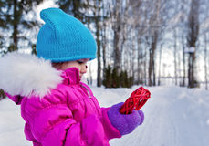 Kleines Mädchen, das an ihrem Handherzthemen Valentinsgruß ` s Tag, der Tag des Winters auf der Straße im Park hält Stockfotografie