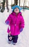 Kleines Mädchen, das an ihrem Handherzthemen Valentinsgruß ` s Tag, der Tag des Winters auf der Straße im Park hält Lizenzfreie Stockfotos