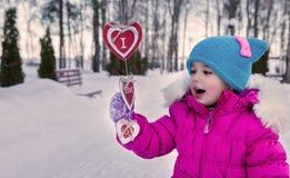 Kleines Mädchen, das an ihrem Handherzthemen Valentinsgruß ` s Tag, der Tag des Winters auf der Straße im Park hält Lizenzfreies Stockbild